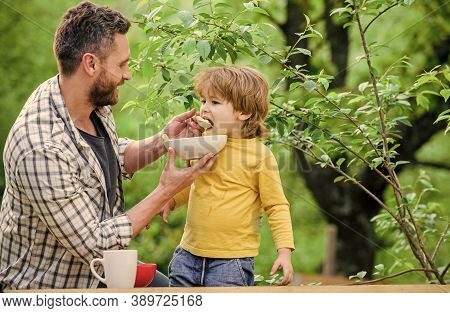 Family And Parenting. Happy Fathers Day. Little Boy With Dad Eat Cereal. Morning Breakfast. Healthy