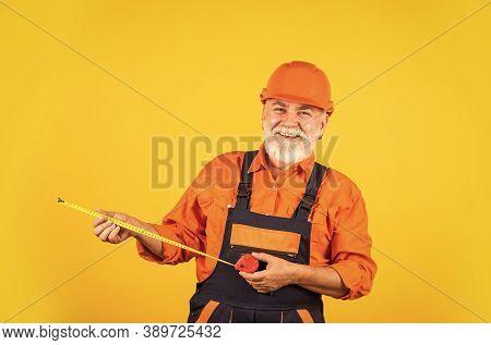 Senior Builder Use Tape-line For Measure. Measurement. Engineer Size Measuring. Construction Man Hol