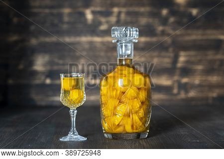 Homemade Tincture Of Yellow Cherry Plum In A Crystal Bottle And Wine Glass On Wooden Background, Ukr