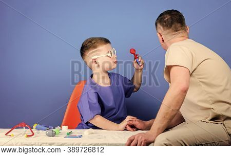 Medicine Concept. Kid Little Doctor Sit Table Medical Tools. Illness Treatment. Dad And Son Medical
