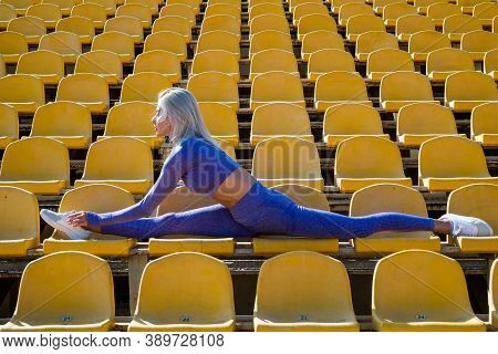 Split. Flexible Woman On Stadium Gym. Female Trainer Do Stretching Workout. Yoga Coach. Sport Succes