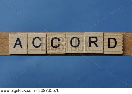 Gray Word Accord In Small Square Wooden Letters With Black Font On A Blue Background