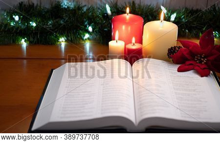 A Bible On The Table In The Light Of A Candles With Pine Cones And Christmas Poinsettia Flowers. Sel