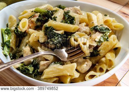 Bowl Of Italian Chicken Penne Alfredo With Kale On Wooden Table