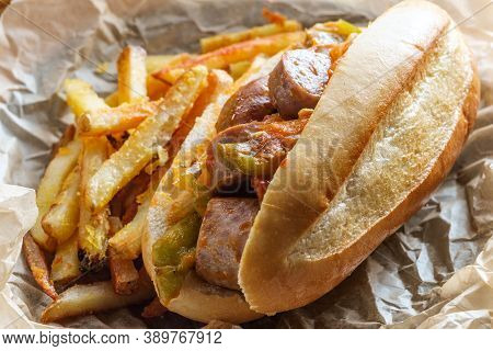 Fried Sausage Onions And Red Green And Yellow Bell Peppers On Sandwich Bun
