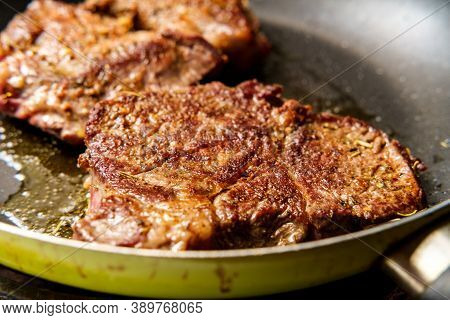 Cooking Fried Steak In Pan With Sizzling Olive Oil