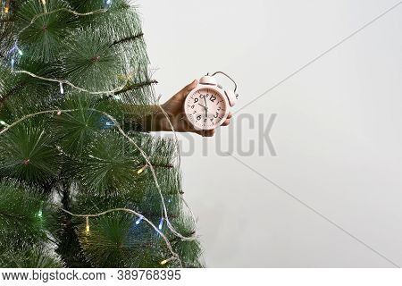 Woman Holding An Alarm Clock Behind The Christmas Tree. Christmas Time. Time To Celebrate Xmas