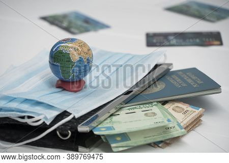 Quarantine In Kazakhstan. Tenge Money With Medical Face Masks, A Globe, A Card And A Passport Are On