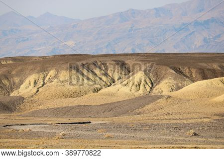 Arid Rolling Hills Besides A Desert Plateau With Barren Mountains Beyond Taken At The Rural Mojave D