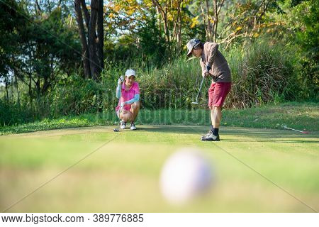 Couple Golf Player Putting Golf Ball On The Green Golf.  Asia Man And Woman Putting Golf Ball On Tee