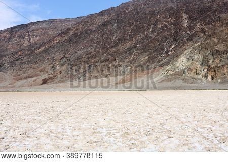 Salt Flats At Badwater Dry Lake Surrounded By Barren Mountains Taken Below Sea Level In Death Valley