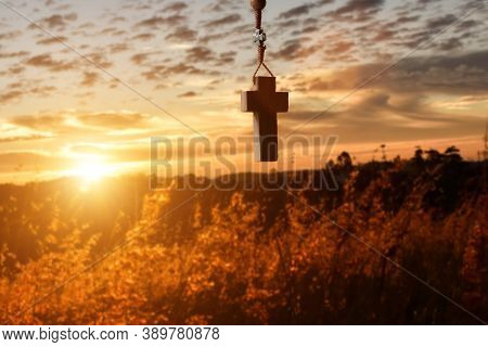 Silhouettes Of Wooden Necklace Christian Cross At Sunset Background. Concept Of Religious, Faith And