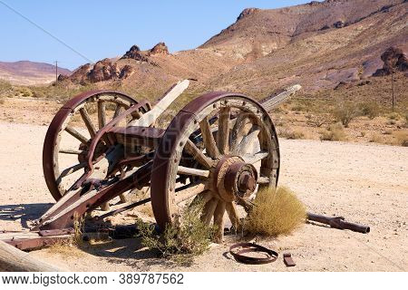 Antique Wooden Wagon Wheels On An Arid Desert Plain With Barren Mountains Beyond Taken At A Ghost To