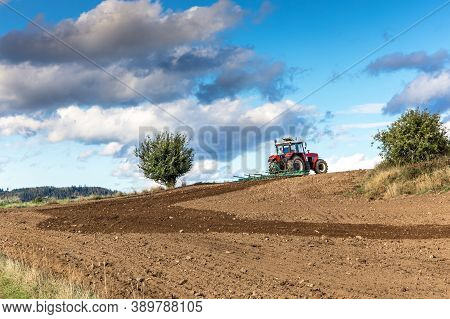 Red Tractor Cultivates The Soil In The Field With A Cultivator After Harvest. Autumn Sunny Day.  Agr