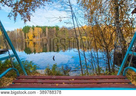 The Swing Is Located In The Forest On The Lake Shore. There Is A Magnificent View Of The Autumn Blue