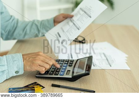 Man Calculates The Debt At Hand With A Calculator. Man Is Stressed And Overthink By Debt From Many C