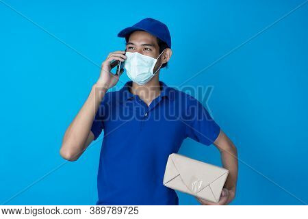 Delivery Man Carries A Package And Talks On The Phone To The Customer To Check The Delivery Address.