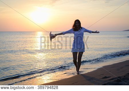 Beautiful Woman Smiling On Beach. Happy People Lifestyle. Woman Smiling In Sunset With Arms Outstret