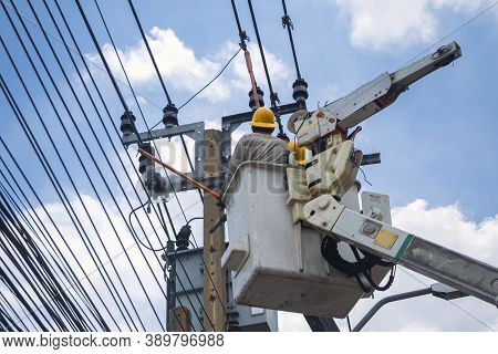 Electricians In Crane Are Working And Installation Of High Voltage Electric Lines, Transformer And T