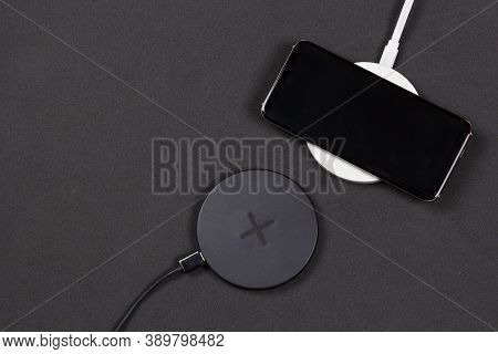Wireless Charging For Phone On Black Background. Smartphone Charges On Fast  Induction Charger.