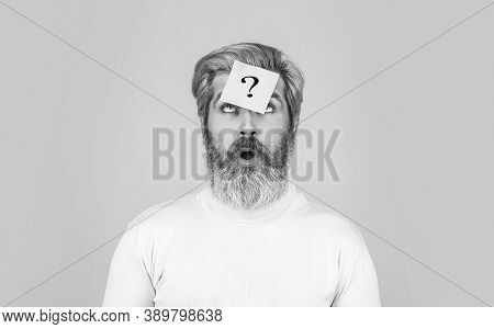 Thinking Bearded Man With Question Mark On Blue Background. Man With Question Mark On Forehead Looki