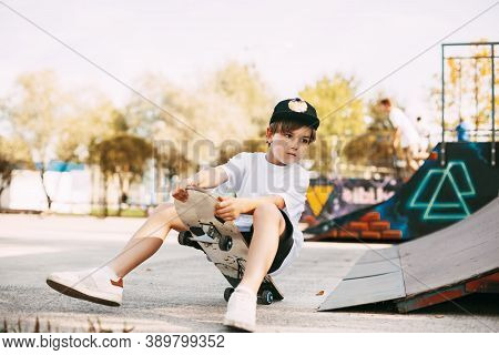 A Boy Performs Tricks On A Skateboard In A Special Area In The Park. A Boy Falls Off A Skate While R