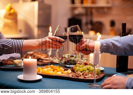 Close Up Of Clinking Glasses With Wine During Romantic Dinner Dinner Celebrating Relationship. Happy