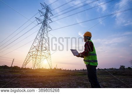Electrical Engineer Standing And Watching At The Electric Power Station To View The Planning Work By