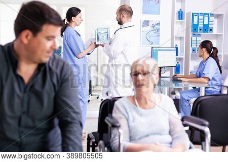 Doctor Using Tablet Pc With Patient X-ray While Discussing With Nurse In Hospital Hallway. Doctor We