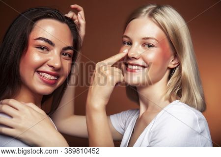 Wo Pretty Diverse Girls Happy Posing Together: Blond And Brunette On Brown Background, Lifestyle Peo