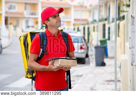 Positive Deliveryman Holding Parcel With Clipboard And Waiting For Recipient Outdoors. Handsome Cauc