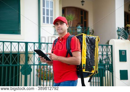 Middle-aged Courier Looking For House And Holding Tablet. Pensive Deliveryman Wearing Red Cap And Sh