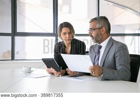 Company Leaders Analyzing Reports. Two Business Colleagues Sitting Together, Looking At Document, Ho