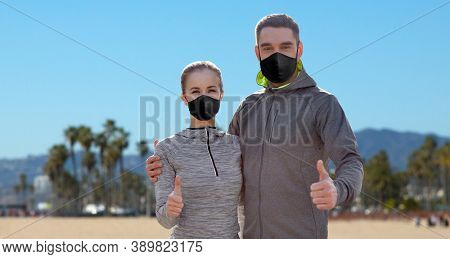 fitness, sport and health concept - couple wearing face protective black reusable masks for protection from virus disease showing thumbs up over venice beach background in california
