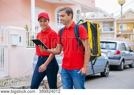Happy Couriers Delivering Order, Working In Express Service And Wearing Red Cap And Shirt. Deliverym