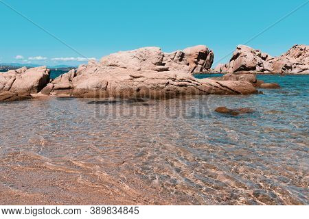 a view of the peculiar rock formations in the coast of Baja Sardinia, in Sardinia, Italy, the clear water of the Mediterranean sea in the foreground and a rock island in the background