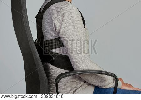 closeup of a young caucasian man wearing an upper back posture corrector as is sitting at his office chair