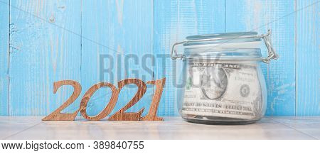 2021 New Year With Money Glass Jar And Wooden Number. Financial, Resolution, Goals, Plan And Saving