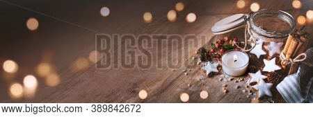 Christmas Decoration With Cinnamon Stars, Baking Ingredients. And Candlelight On Wood. Horizontal Ba