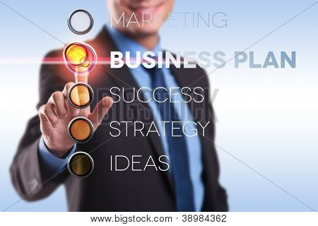 business man making a choice by pushing a business plan button