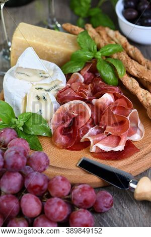 Antipasto. Wine Set Snacks Of Dried Ham, Brie Cheese With Mold, Parmesan With Grissini, Olives And P