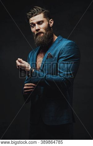 Bearded And Serious Business Person Dressed In Blue Custom Suite Posing Holding His Jacket Sleeve In