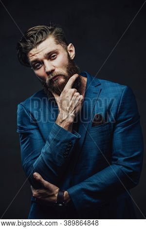 Dressed In Modern Custom Suite Guy With Beard And Stylish Haircut Posing In Dark Background With Han
