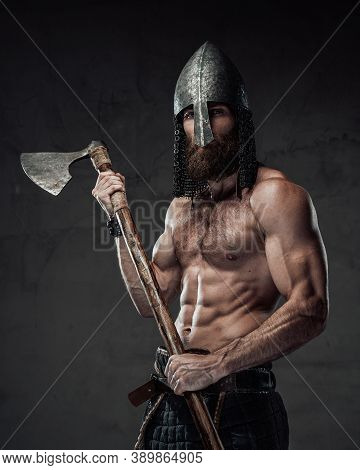 Furious And Muscular Nord Warrior Standing In Dark Background With Naked Torso And With His Two Hand