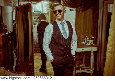 Portrait of a smiling wealthy mature man in an elegant suit and modern sunglasses in a luxury apartment. Male beauty, fashion. Optics, sunglasses for men.