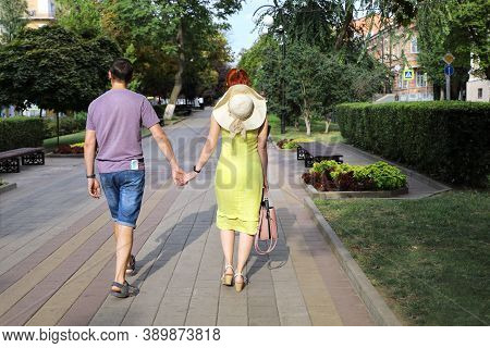 Young Couple Is Walking Holding Hands Along Deserted Alley Of The City On Summer Sunny Day. Full-len