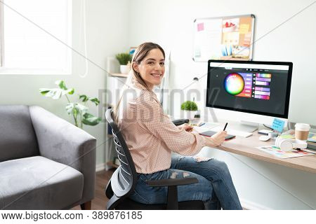 Attractive Woman Working As A Graphic Designer With A Graphic Tablet And Choosing The Right Colors