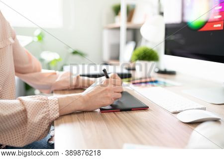 Profile View Of The Hands Of A Woman Working As A Designer And Using A Graphic Tablet In Her Office