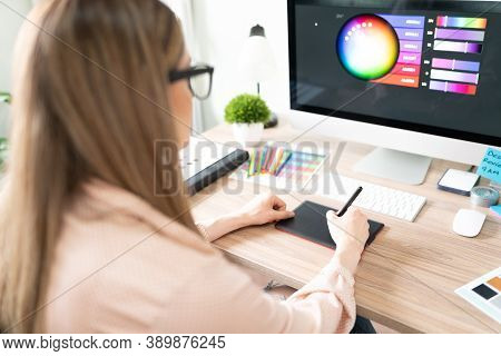 Rear View Of A Female Graphic Designer Using A Graphic Tablet And Choosing The Right Color For A Des