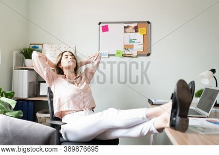 Full Length View Of A Woman Dressed Casual And Relaxing In Her Office With Her Feet Up The Desk And